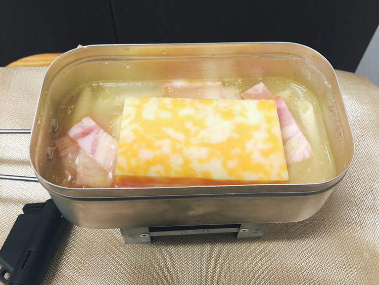 オリーブオイルとニンニクチューブを入れてかき混ぜ、上にナチュラルチーズをのせる